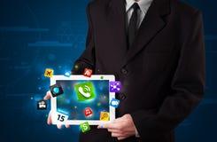 Affärsman som rymmer en minnestavla med moderna färgrika apps och symboler Arkivbilder