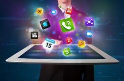Affärsman som rymmer en minnestavla med moderna färgrika apps och symboler Royaltyfri Bild