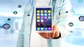 Affärsman som rymmer en minnestavla som omger vid app och den sociala symbolen Arkivfoton