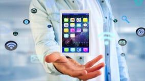 Affärsman som rymmer en minnestavla som omger vid app och den sociala symbolen Fotografering för Bildbyråer