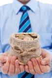 Affärsman som rymmer en påse av euromynt Arkivfoton