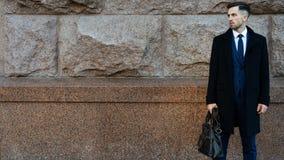 Affärsman som rymmer en portfölj nära väggen Sök efter bakgrund arkivfoton