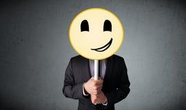 Affärsman som rymmer en smileyframsidaemoticon Arkivfoton