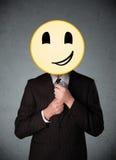 Affärsman som rymmer en smileyframsidaemoticon Royaltyfri Fotografi