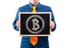 Affärsman som rymmer en svart tavla med bitcoinsymbol Fotografering för Bildbyråer