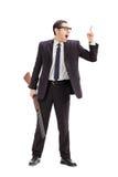 Affärsman som rymmer ett gevär och gör en gest med fingret Fotografering för Bildbyråer