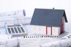 Affärsman som rymmer ett silvermagasin med en konstgjord modell av huset Arkivfoton