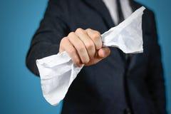 Affärsman som rymmer ett skrynkligt ark av papper A4 close upp Isolator royaltyfria foton