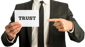 Affärsman som rymmer ett vitt kort som säger förtroende Arkivbild