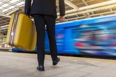 Affärsman som rymmer hans handväska och går i statio för himmeldrev fotografering för bildbyråer