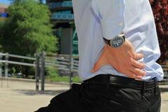 Affärsman som rymmer hans lägre baksida Smärta lättnadsbegreppet Fotografering för Bildbyråer