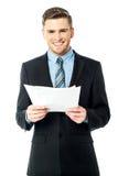 Affärsman som rymmer viktiga avtalsdokument Arkivbild