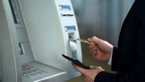 Affärsman som sätter in kreditkorten i ATM för att motta pengar som återtar kassa royaltyfria foton
