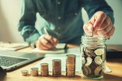 affärsman som sätter mynt in i tillbringareexponeringsglas sparande pengar för begrepp arkivfoton