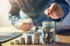 affärsman som sätter mynt in i tillbringareexponeringsglas sparande pengar för begrepp royaltyfri foto