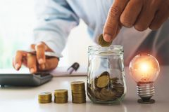 Affärsman som sätter myntet i glasflaskabesparingbanken och accoun arkivfoto