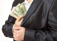 Affärsman som sätter pengar i dräktomslagsfack royaltyfria foton