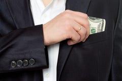Affärsman som sätter pengar i fick- dräkt royaltyfria foton