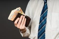 Affärsman som sätter sedlar i hans plånbok Bunt av femtio euro pengar Affärsmannen är hållande kassa Personlöner i euroräkningar royaltyfri foto