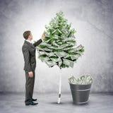 Affärsman som samlar pengar från träd Arkivbild