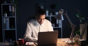 Affärsman som sent arbetar - natt på kontorsbärbara datorn stock video