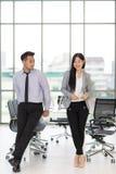 Affärsman som ser affärskvinnan i modernt kontor royaltyfri bild