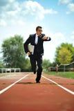 Affärsman som ser armbandsurklockaspring på idrotts- spår i spänning Arkivbilder