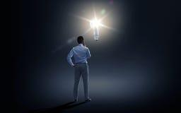 Affärsman som ser belysningkulan över mörker Royaltyfria Bilder