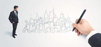 Affärsman som ser den hand drog staden på väggen Arkivfoto