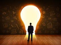 Affärsman som ser den ljusa ljusa kulan i väggen Arkivfoton