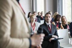 Affärsman som ser den offentliga högtalaren under seminarium Royaltyfri Fotografi