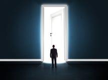 Affärsman som ser den stora ljusa öppnade dörren arkivbild
