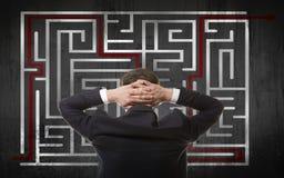 Affärsman som ser en labyrint Arkivbild