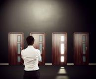 Affärsman som ser fyra dörrar Arkivfoton
