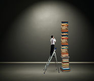 Affärsman som ser högen av böcker Royaltyfri Foto