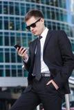 Affärsman som ser hans telefonassistent och royaltyfria bilder