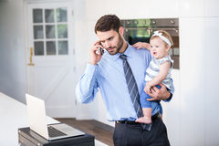 Affärsman som ser i bärbar dator, medan bära dottern arkivfoton