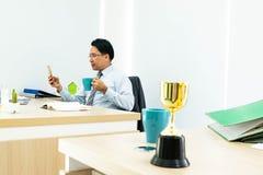 Affärsman som ser mobiltelefonen arkivfoto