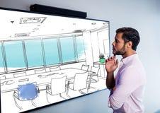 affärsman som ser skärmen på väggen och tänker på den nya desingen av den nya mötesrummet royaltyfri bild