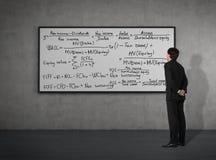 Affärsman som ser till matematiska formler Arkivfoto