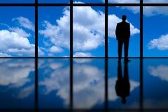 Affärsman som ser ut ur högt löneförhöjningkontorsfönster på blå himmel och moln Royaltyfria Bilder