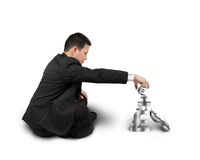 Affärsman som sitter och staplar symboler för pengar 3D Royaltyfri Bild
