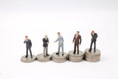 Affärsman som skakar på myntbuntar Royaltyfri Bild