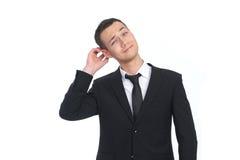 Affärsman som skrapar hans huvud Arkivfoto