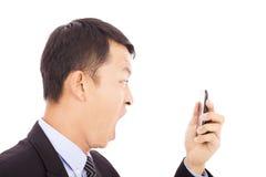 Affärsman som skriker in i den smarta telefonen över vit Arkivbild