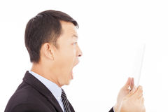 Affärsman som skriker in i ipad eller minnestavlan över vit Arkivfoto