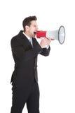 Affärsman som skriker in i megafonen Fotografering för Bildbyråer