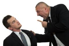 Affärsman som skriker och slåss på en ung kollega arkivfoton