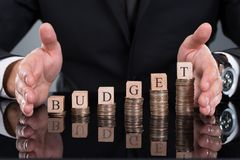 Affärsman som skyddar budget- kvarter på staplade mynt Fotografering för Bildbyråer