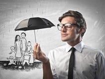 Affärsman som skyddar en familj från regnet Arkivbild
